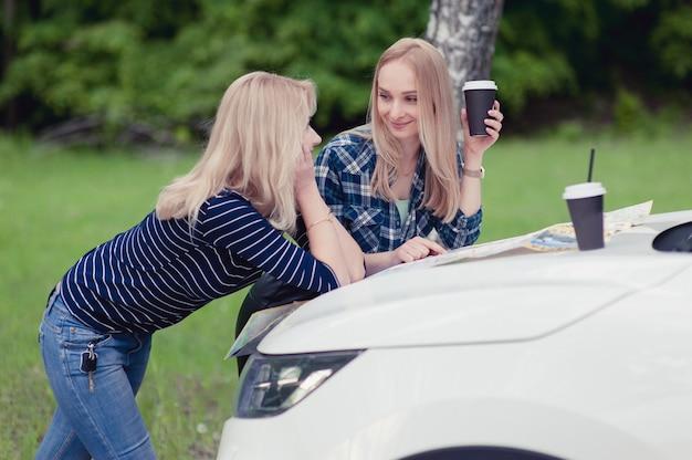 Due ragazze si fermarono sulla strada per ottenere indicazioni stradali e bere un caffè Foto Premium