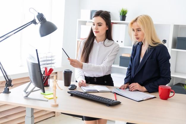 Due ragazze stanno nell'ufficio vicino al tavolo e guardano il monitor. Foto Premium