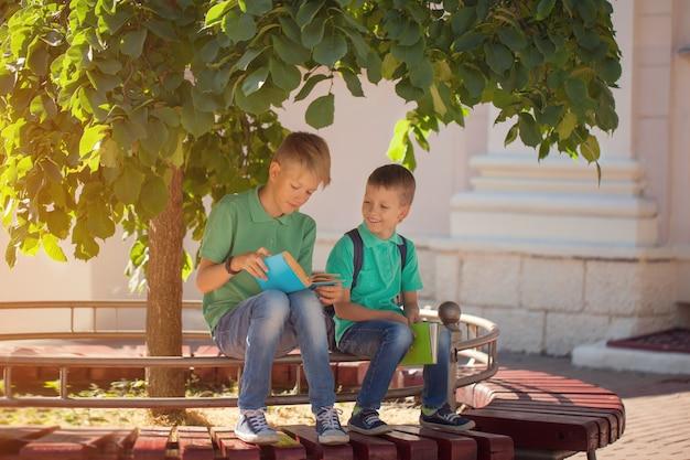 Due ragazzi del bambino della scuola che si siedono sotto un albero e leggono i libri un giorno di estate soleggiato Foto Premium