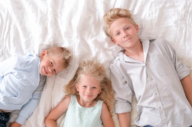 Due ragazzi e ragazze biondi sono distesi insieme sul letto, guardando e sorridendo. Foto Premium