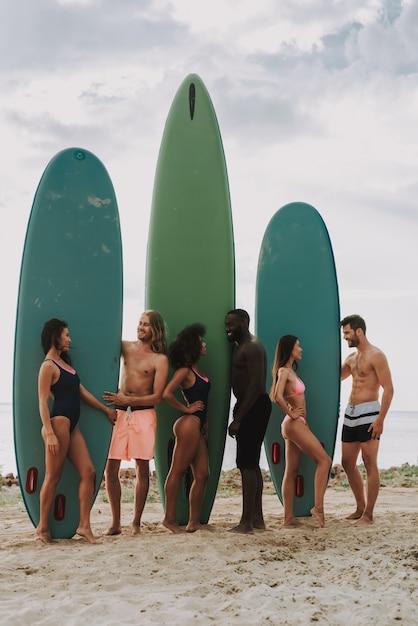 Due ragazzi in spiaggia tiene surf. ragazze in costume da bagno. Foto Premium