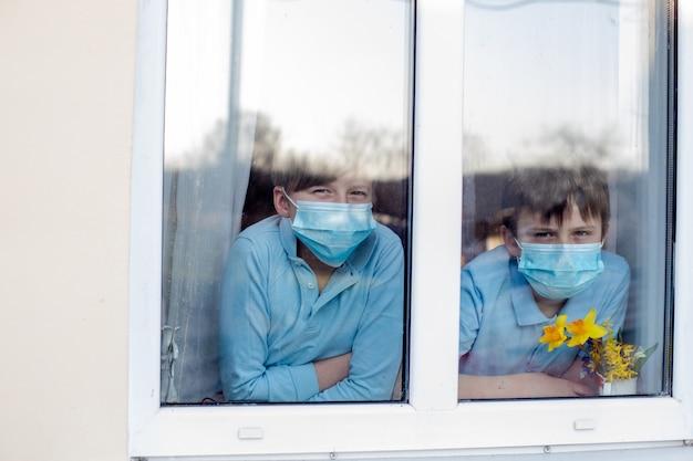 Due ragazzi nelle maschere mediche della procedura del ciclo dell'orecchio guardano fuori dalla finestra della casa. i bambini rimangono a casa durante la pandemia di coronavirus in quarantena. Foto Premium