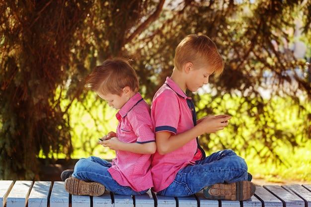 Due ragazzini che giocano sul telefono cellulare nel giorno soleggiato, sitt Foto Premium