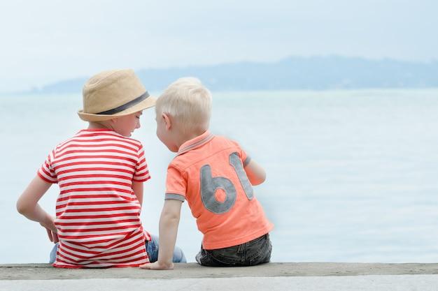 Due ragazzini siedono su un molo, contro il mare e le montagne. vista posteriore Foto Premium