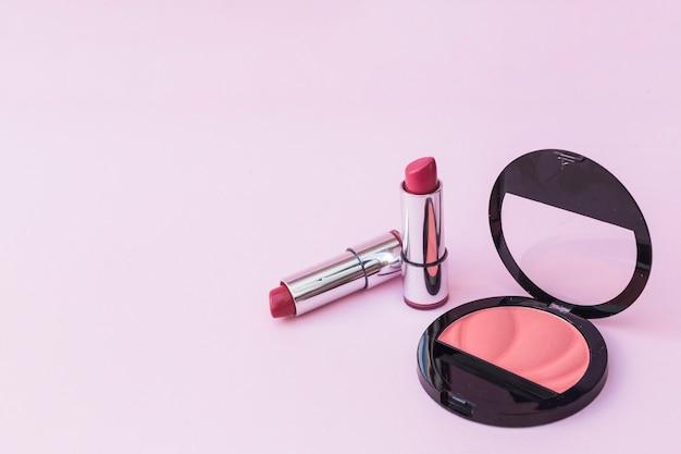 Due rossetti e fard rosa su sfondo rosa Foto Gratuite