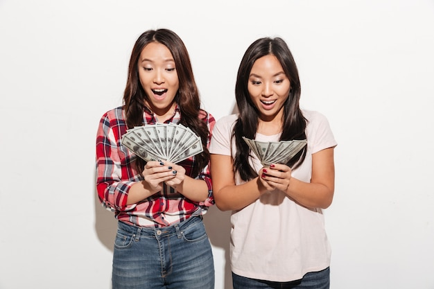 Due signore sveglie abbastanza colpite asiatiche che tengono soldi. Foto Gratuite