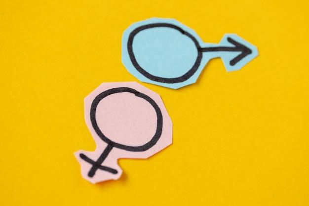 Due simboli di genere venere e marte tagliati da carta blu e rosa Foto Premium