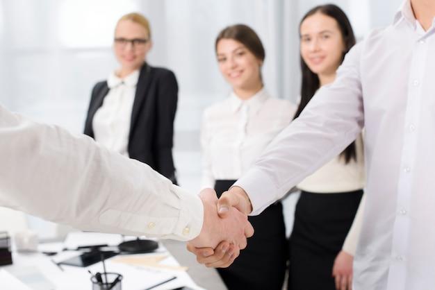 Due soci d'affari si stringono la mano in ufficio Foto Gratuite