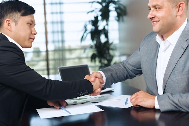 Due soci in affari che si siedono insieme ad un tavolo e che lavorano. Foto Premium