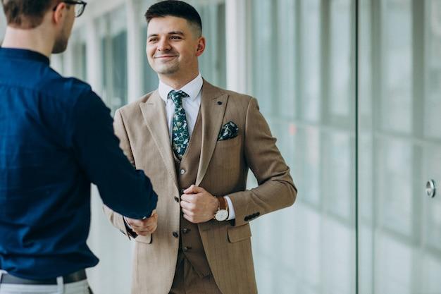 Due soci maschi che stringono le mani all'ufficio Foto Gratuite