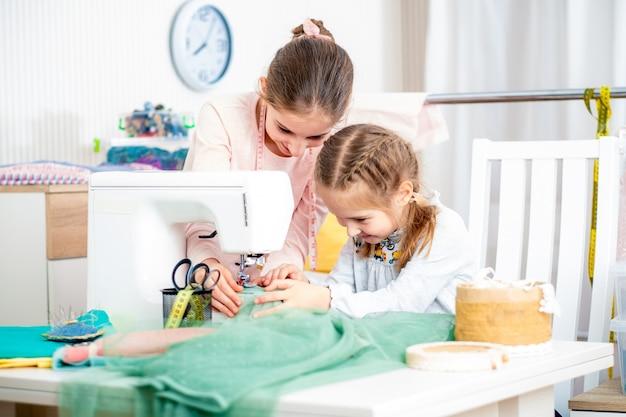 Due sorelle che lavorano su una macchina da cucire Foto Premium
