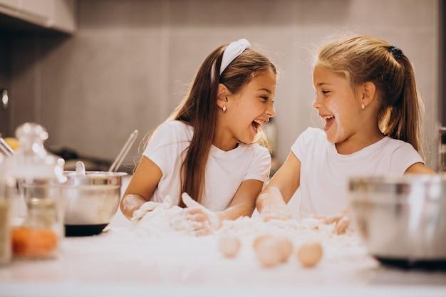 Due sorelle delle bambine che cucinano alla cucina Foto Gratuite