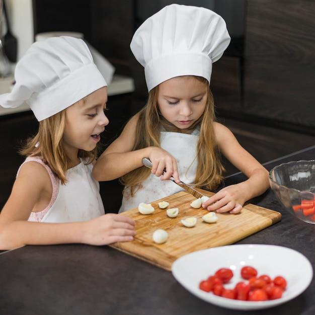 Due sorelle in cappello del cuoco unico e grembiule che tagliano uova sode sul tagliere di legno Foto Gratuite