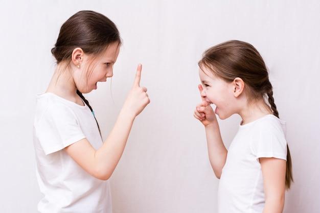 Due sorelle ragazze litigano fortemente l'una con l'altra Foto Premium