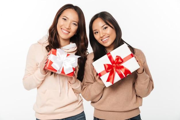 Due sorelle sveglie asiatiche delle signore che tengono i contenitori di regalo sorprendono. Foto Gratuite