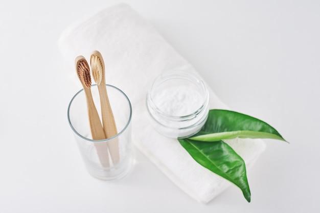 Due spazzolini da denti amichevoli di bambù di legno di eco in un vetro, bicarbonato di sodio e asciugamano su fondo bianco. Foto Premium
