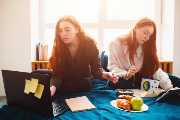 Due studenti dai capelli rossi studiano a casa o si preparano per gli esami. giovani donne che fanno i compiti in un dormitorio vicino alla finestra. ci sono quaderni, libri alimentari, tablet e laptop e documenti Foto Premium