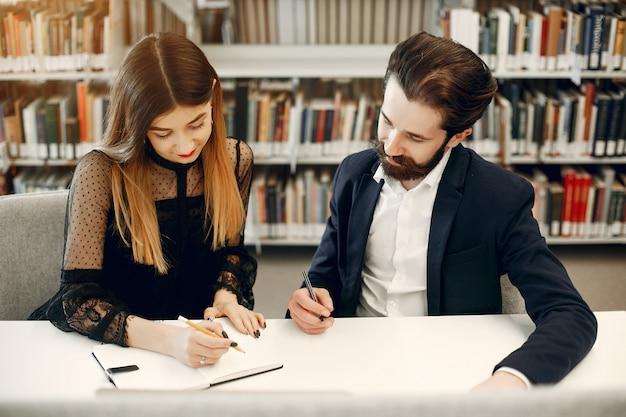 Due studenti studiano in biblioteca Foto Gratuite