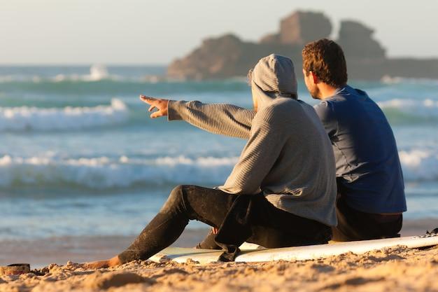 Due surfisti che parlano sulla spiaggia Foto Premium