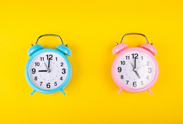 Due sveglie su uno sfondo giallo brillante che mostra tempi diversi come il concetto di inizio e fine della giornata lavorativa Foto Premium