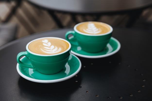 Due tazze blu-chiaro hanno riempito di caffè dell'aroma sulla tavola nera Foto Premium