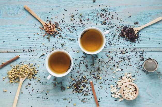 Due tazze di tè in ciotola di ceramica con fiori di crisantemo cinese secchi ed erbe sul tavolo Foto Gratuite