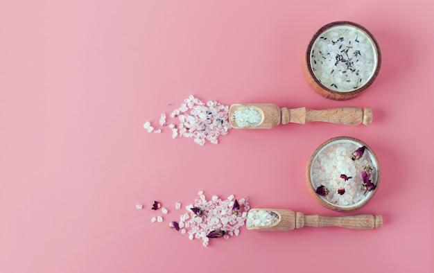 Due tipi di sali da bagno himalayan e spa. trattamento spa. l'industria del relax. cristalli da bagno in un piatto di legno. piatto giaceva su uno sfondo rosa con copia spazio banner. zero sprechi. rosa, lavanda Foto Premium