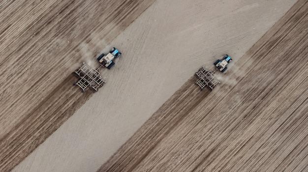 Due trattori solcano il campo di vista dall'alto Foto Premium