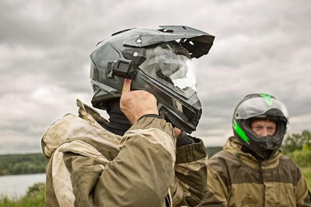 Due uomini all'aperto indossano caschi e uniformi da moto. Foto Premium