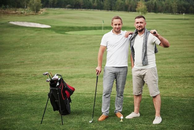 Due uomini alla moda che tengono le borse con i club e che camminano sul campo da golf Foto Premium
