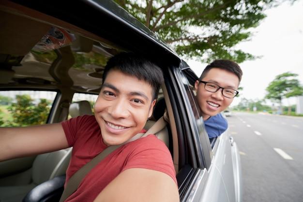 Due uomini asiatici che guidano in automobile sulla strada e che guardano fuori e autista che prende selfie Foto Gratuite