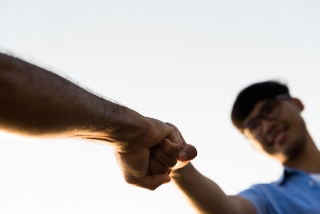 Due uomini che danno urto di pugno mostrando unità e lavoro di squadra. amicizia, concetto di partnership. Foto Premium