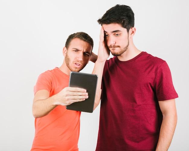 Due uomini che guardavano perplessi lo schermo del tablet Foto Gratuite