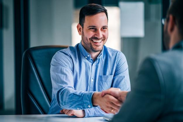 Due uomini d'affari sorridenti che stringono le mani mentre sedendosi alla scrivania. Foto Premium