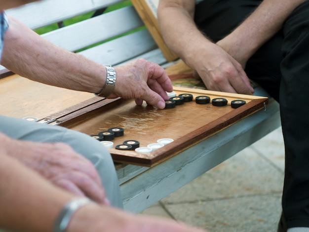 Due uomini senior che giocano tavola reale sul banco nella fine della via su Foto Premium