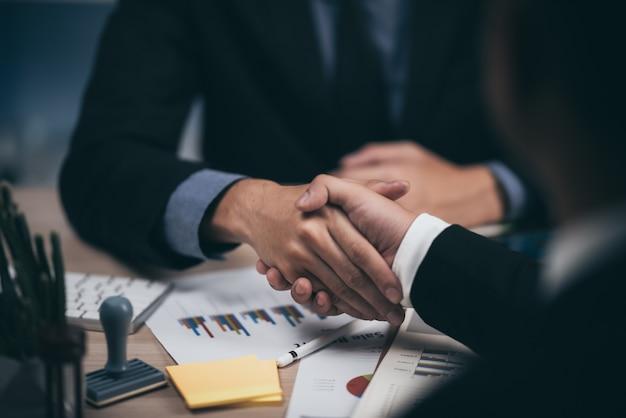 Due uomini sicuri di affari che stringono le mani nel corso di una riunione nel concetto dell'ufficio, di successo, di affare, di saluto e del partner. Foto Premium