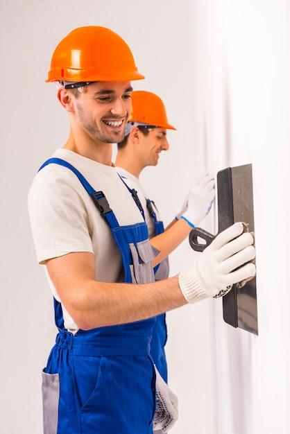 Due uomini stucco un muro bianco in un nuovo appartamento. Foto Premium