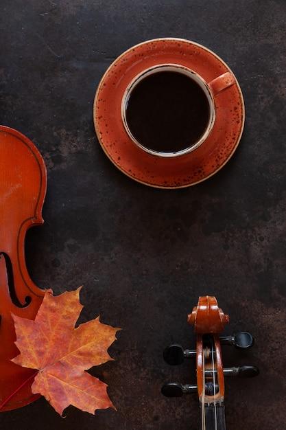 Due vecchi violini, una tazza di caffè e una foglia d'acero in autunno Foto Premium