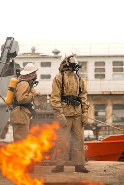 Due vigili del fuoco usano il lavoro di squadra in un allenamento per fermare il fuoco in una missione pericolosa e proteggere l'ambiente Foto Premium