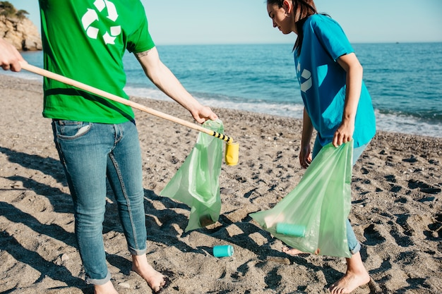 Due volontari che raccolgono rifiuti in spiaggia Foto Gratuite