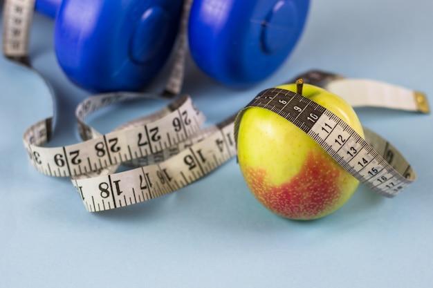 Dumbbells blu, nastro di misurazione e mela su una priorità bassa blu. uno stile di vita sano Foto Premium