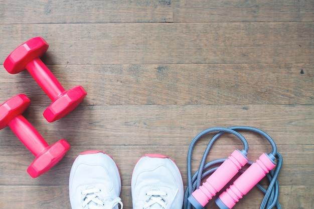 Dumbbells rossi, corda di salto e scarpe sportive su sfondo di legno con copia spazio, concetto di stile di vita sano Foto Premium