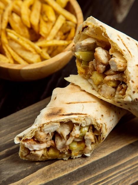 Durum di pollo, shaurma all'interno di lavash con patatine fritte su tavola di legno Foto Gratuite
