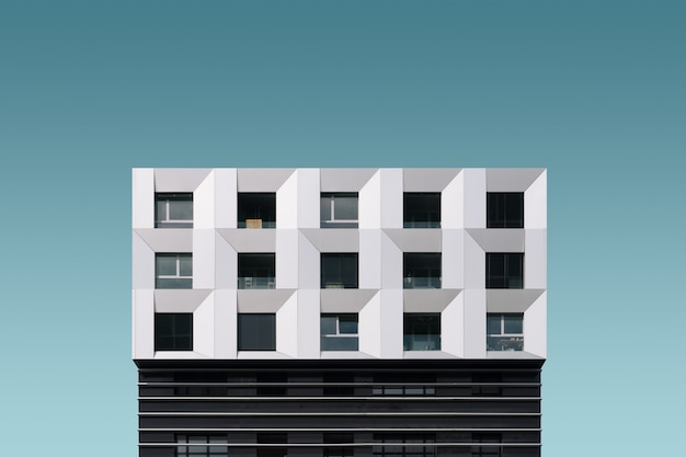 Edificio moderno in metallo argento e nero sotto il cielo blu Foto Gratuite