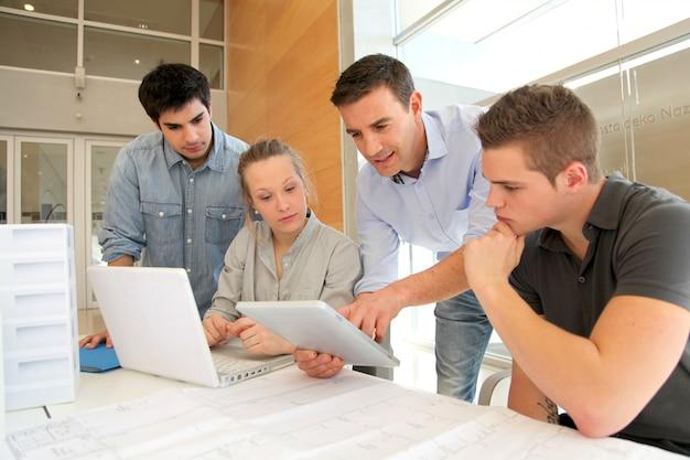 Educatore con studenti in architettura che lavorano su tablet elettronico Foto Premium