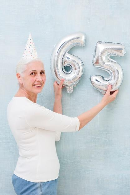 Elder bella donna che tiene il numero di palloncino stagnola sul suo compleanno Foto Gratuite