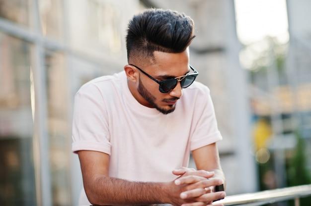 Elegante barba uomo in occhiali da sole e maglietta rosa modello india poste all'aperto in strada della città Foto Premium