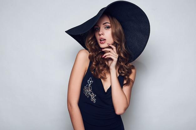 Elegante bella donna in un abito nero e cappello Foto Premium