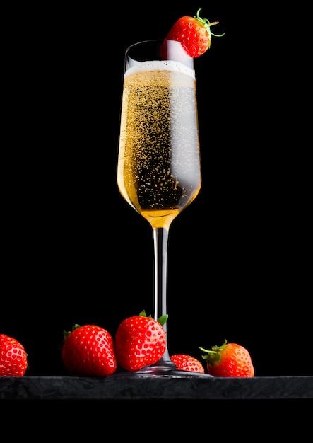 Elegante bicchiere di champagne giallo con fragole in cima e bacche fresche sul bordo di marmo nero su fondo nero. Foto Premium