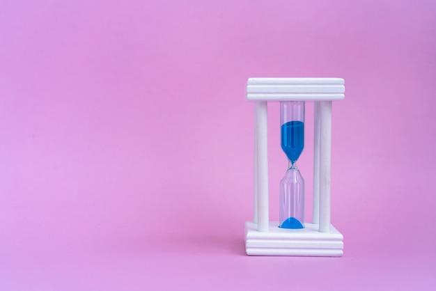 Elegante clessidra con l'esecuzione di sabbia blu su sfondo rosa con copia Foto Premium